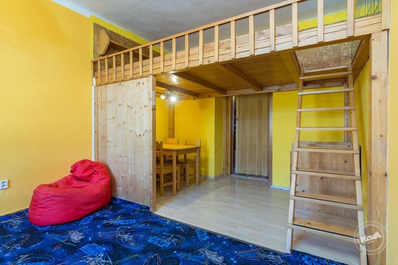 Světlá ložnice s vestavěným patrem na spaní a jídelním koutem